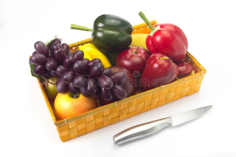 Cesta de fruta falsa con un cuchillo en un fondo blanco. imagenes de archivo