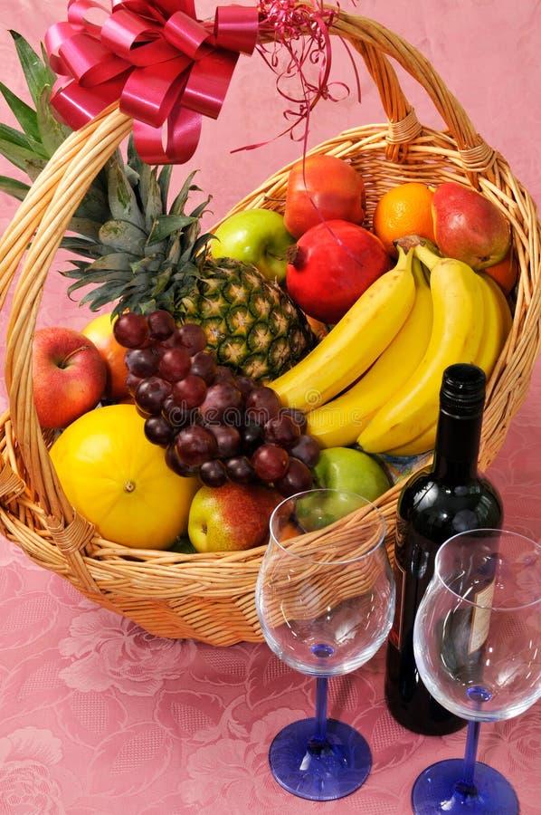 Cesta de fruta y una botella de vino foto de archivo libre de regalías