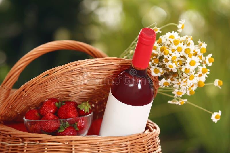 Cesta de la comida campestre con el vino, las fresas y las flores en fondo borroso fotos de archivo libres de regalías