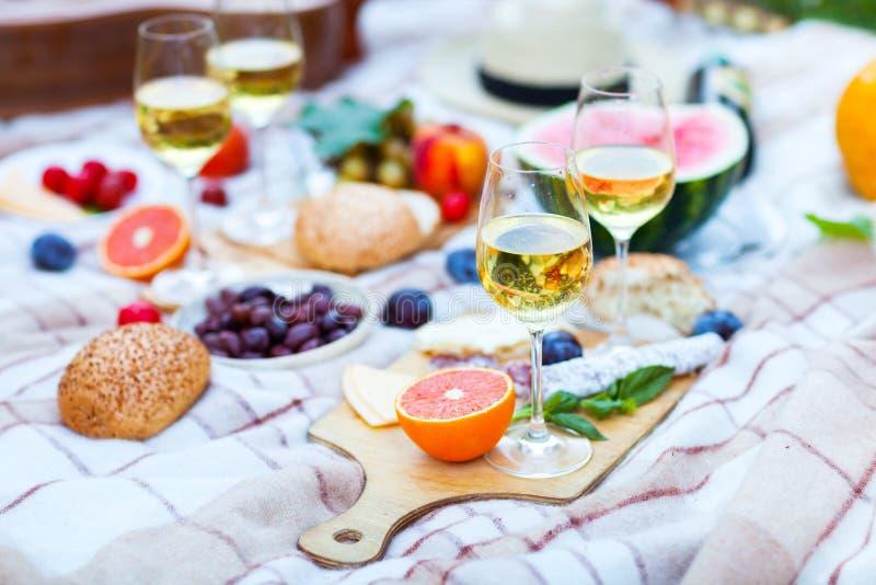 Cesta de la comida campestre del verano en la hierba verde Alimento y concepto de la bebida foto de archivo