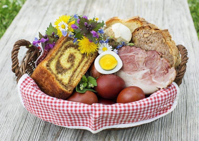 Cesta de la comida de Pascua con los huevos y el jamón fotografía de archivo libre de regalías