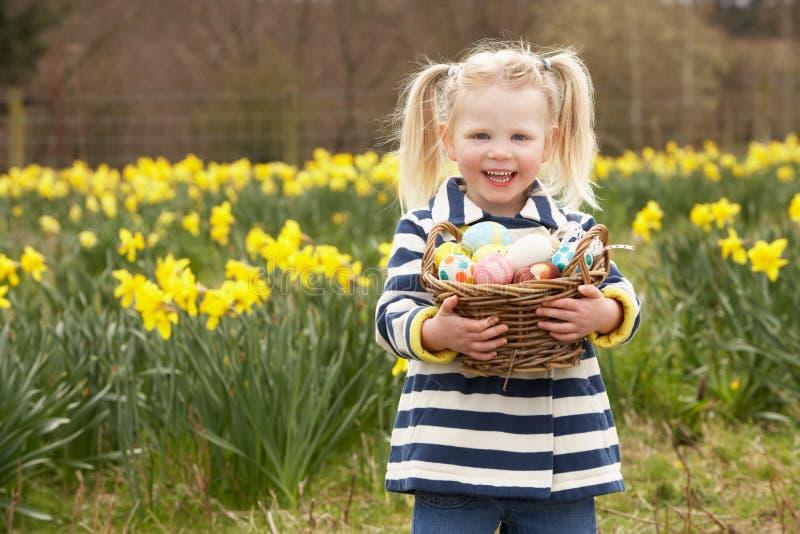 Cesta de la explotación agrícola de la chica joven de huevos adornados fotografía de archivo libre de regalías