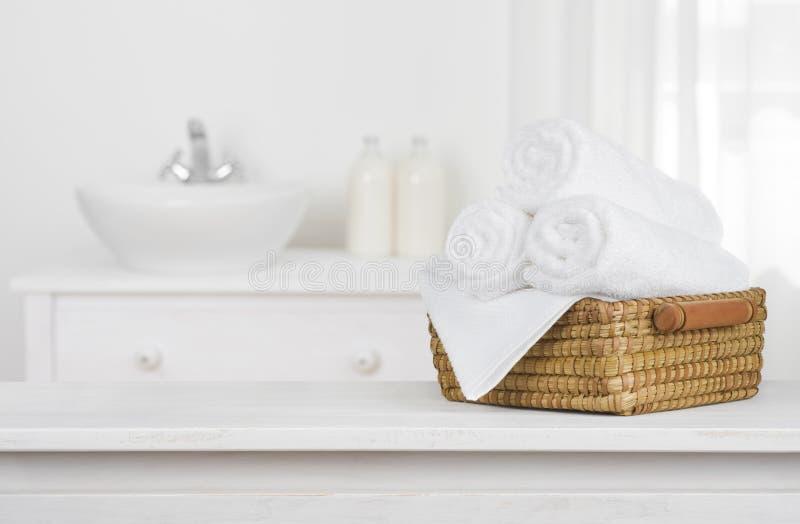 Cesta de las toallas en la sobremesa de madera con el interior borroso del cuarto de baño imagen de archivo