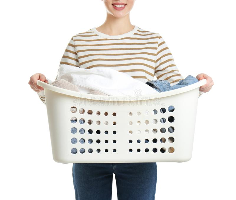 Cesta de lavadero de la tenencia de la mujer joven con ropa en el fondo blanco fotos de archivo