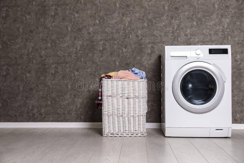 Cesta de lavadero de mimbre por completo de ropa y de lavadora sucias cerca de la pared del color fotos de archivo libres de regalías