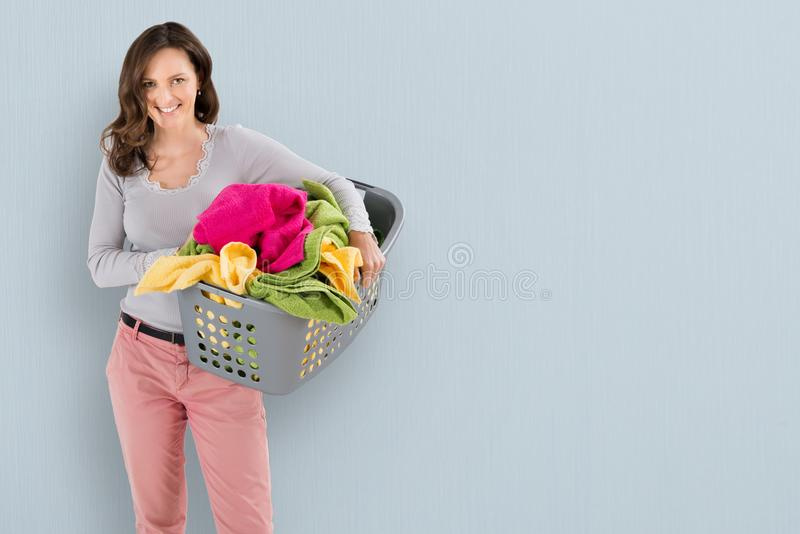 Cesta de lavanderia carreg da mulher imagens de stock