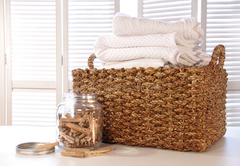 Cesta de lavanderia com linhos na tabela imagens de stock