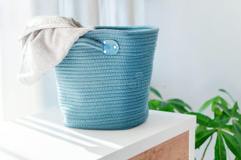 Cesta de lavanderia com toalha cinzenta Interior da sala ? moda branca com cesta de lavanderia imagens de stock royalty free