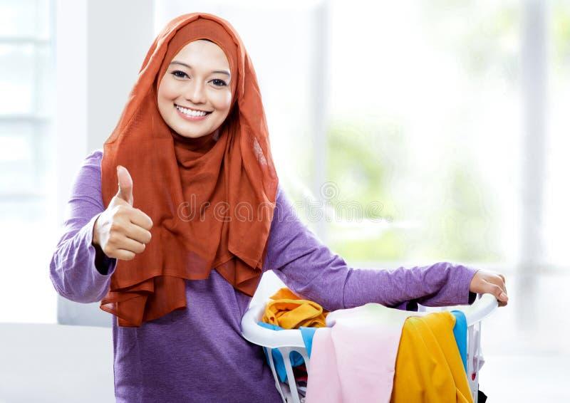 Cesta de lavanderia levando vestindo de sorriso bonita do hijab da mulher imagem de stock royalty free