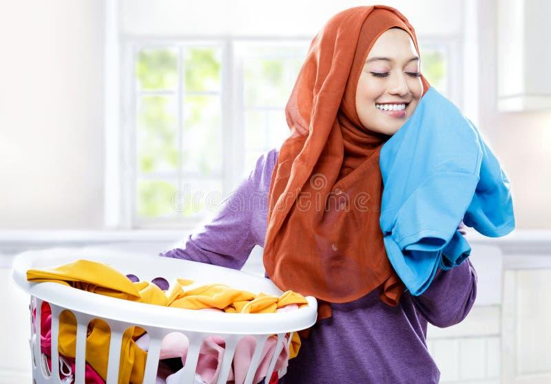 Cesta de lavanderia levando vestindo do hijab da jovem mulher ao cheirar foto de stock