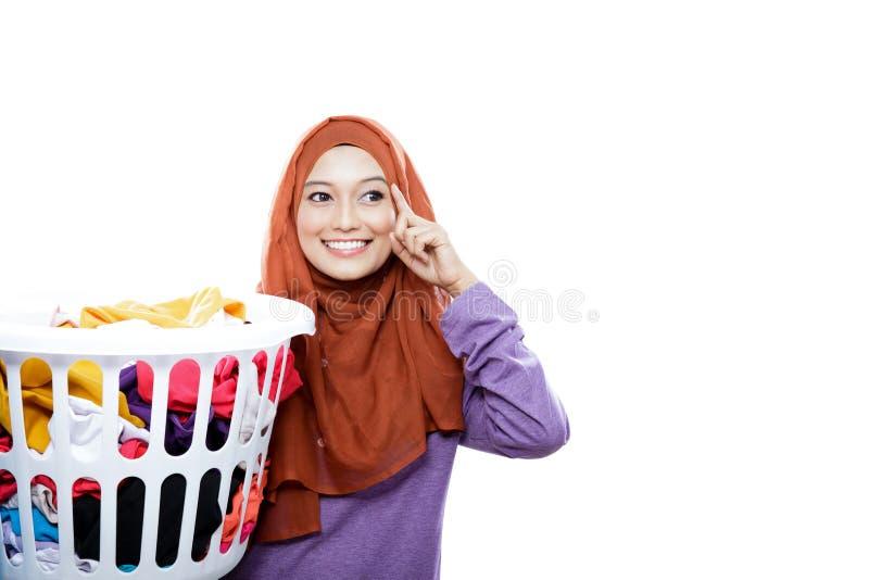 Cesta de lavanderia levando vestindo do hijab da mulher bonita com mão imagem de stock