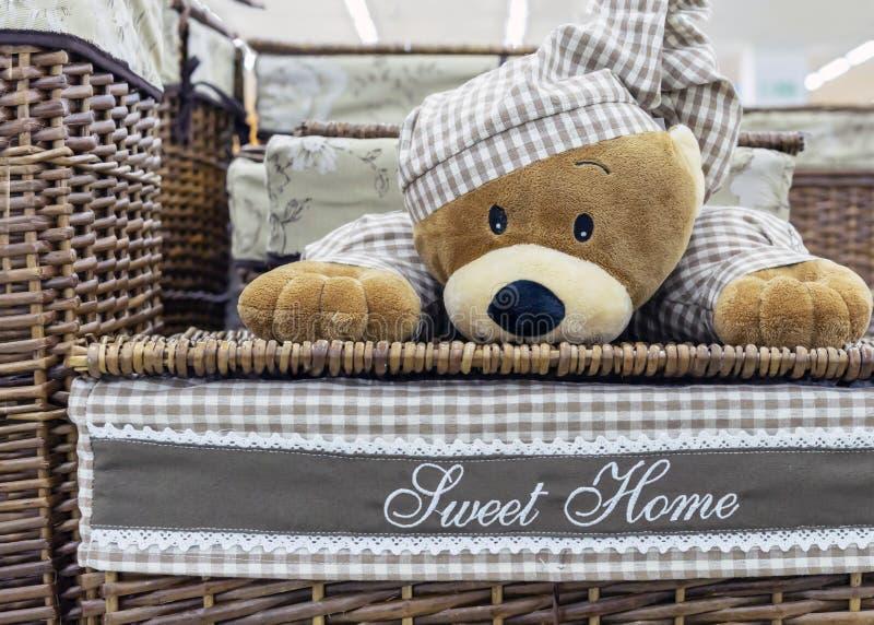 Cesta de lavanderia de vime com um urso de peluche em pijamas quadriculados foto de stock royalty free