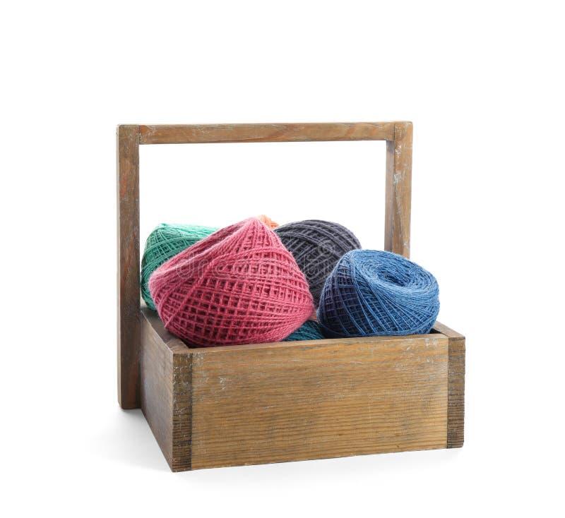 Cesta de madeira com clews de linhas de confecção de malhas coloridas imagem de stock