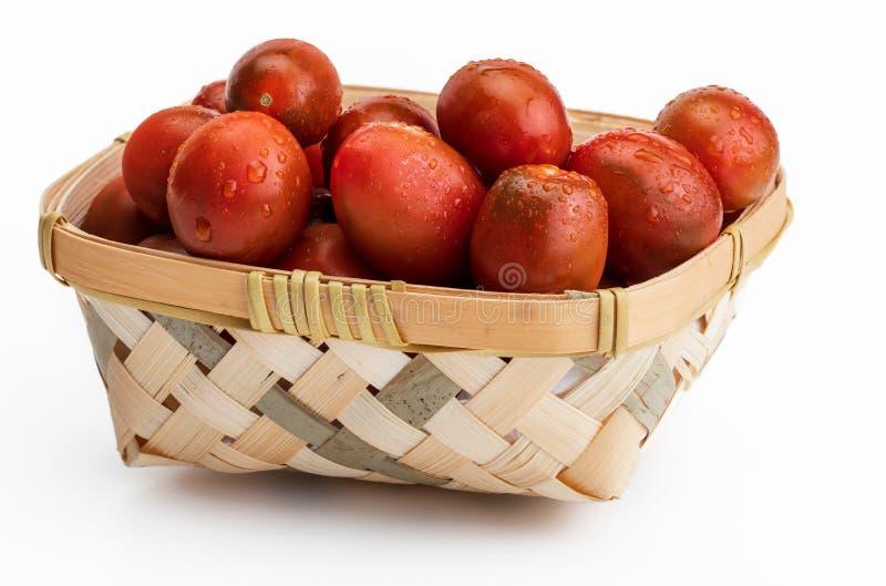 Cesta de mimbre con kumakos de los tomates de cereza los mini cortados en medio y entero Con descensos del agua libre illustration