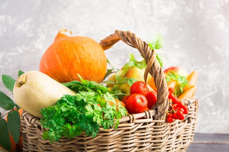 Cesta de mimbre con las frutas y verduras del otoño en fondo gris fotografía de archivo libre de regalías