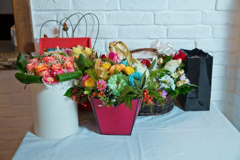 Cesta de mimbre con las rosas, las flores y las fresas maduras rojas Ramos color de rosa maravillosamente adornados Ramos colorid fotos de archivo