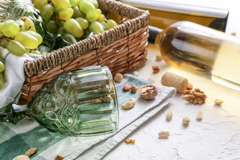 Cesta de mimbre con las uvas y las copas maduras en la tabla blanca imagenes de archivo