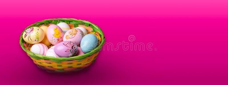 Cesta de mimbre con los huevos de Pascua pintados a mano en fondo tablero del color imagenes de archivo