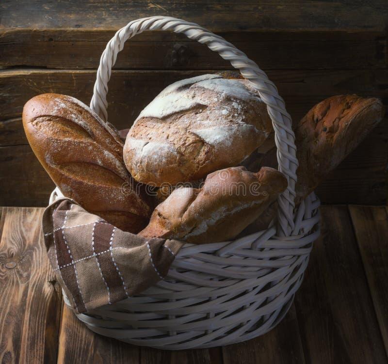 Cesta de mimbre con pan fresco en una tabla de madera fotografía de archivo libre de regalías