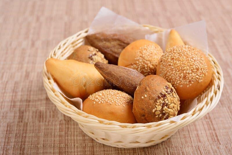 Cesta de mimbre con pan Pan y bollos dentro de la cesta Productos frescos de la panader?a en la tabla Prueba el mejor cuando es c fotografía de archivo