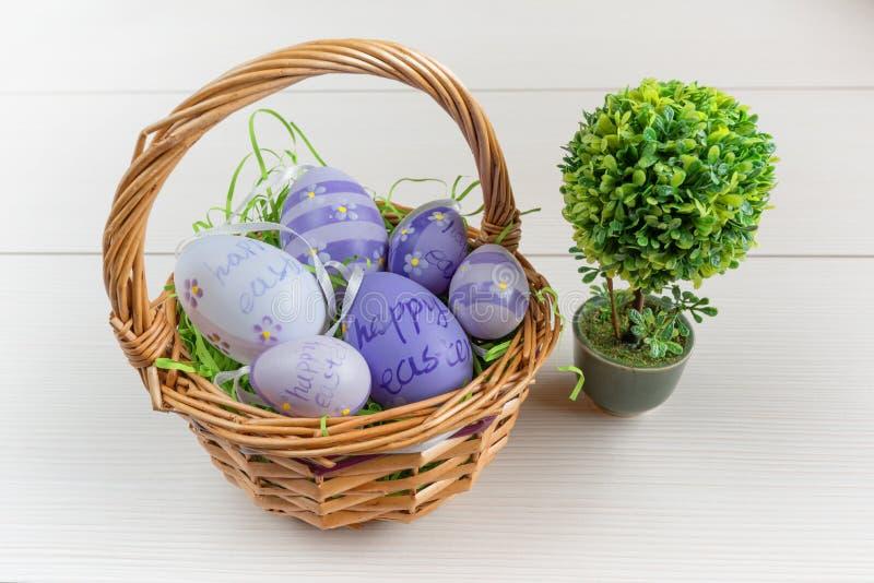 Cesta de mimbre de Pascua con huevos coloreados y un pequeño bonsai en el tablero de madera foto de archivo libre de regalías