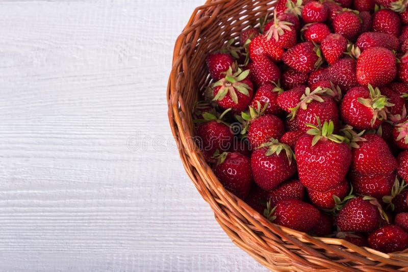 Cesta de mimbre llenada de las fresas maduras En un fondo de madera blanco Copia-espacio fotografía de archivo libre de regalías
