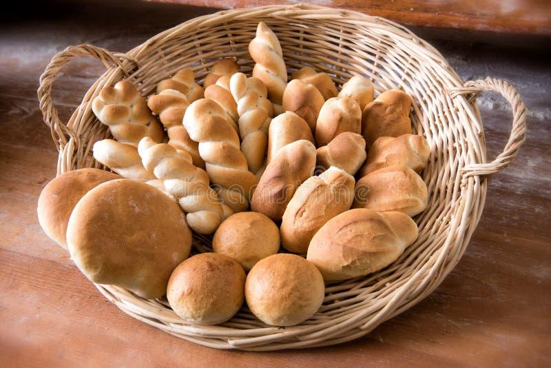 Cesta de mimbre llenada de pan recientemente cocido imagen de archivo