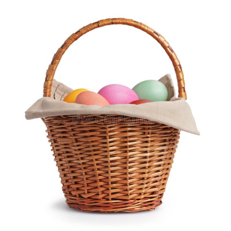 Cesta de mimbre por completo de huevos de Pascua de los colores en colores pastel fotografía de archivo