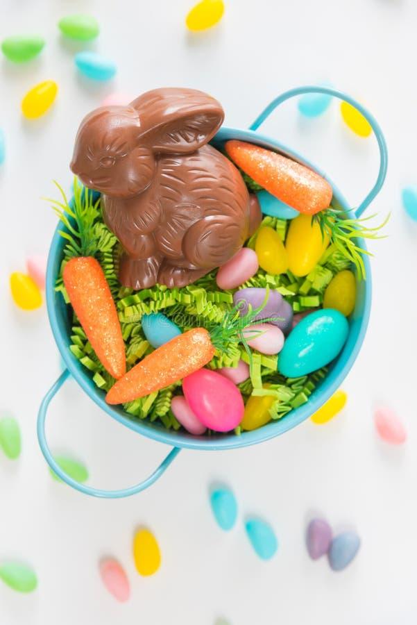 Cesta de Pascua con el conejo del chocolate, los huevos de caramelo, y las mini zanahorias en el fondo blanco con los jellybeans foto de archivo libre de regalías