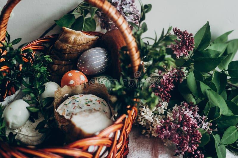 Cesta de Pascua con la comida de la torta y del jamón de los huevos colorido adornado eg. fotografía de archivo