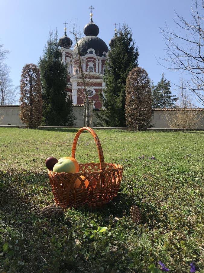 Cesta de Pascua con la fruta y los huevos en la hierba fotografía de archivo