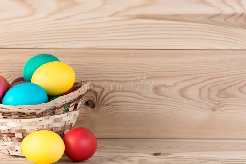 Cesta de Pascua con los huevos coloreados y lugar para una inscripción fotos de archivo libres de regalías