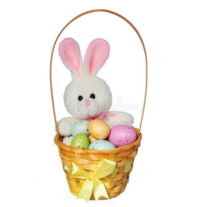 Cesta de Pascua con los huevos coloridos y el juguete del conejito aislado fotos de archivo libres de regalías