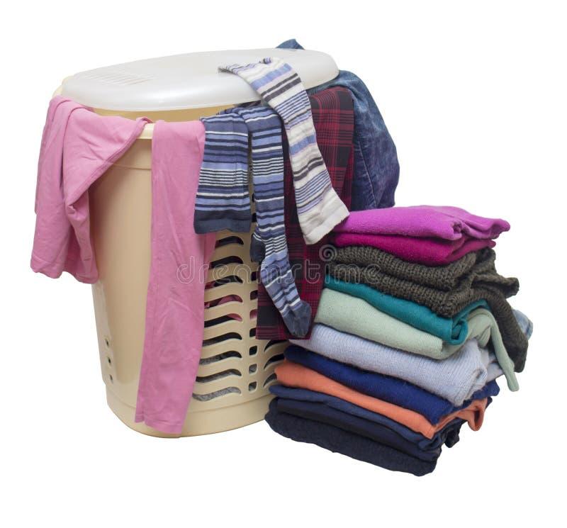 Cesta de ropa de plástico, desde debajo de la cubierta de la cual se pueden ver diferentes ropas y un montón de ropa al lado del  fotografía de archivo