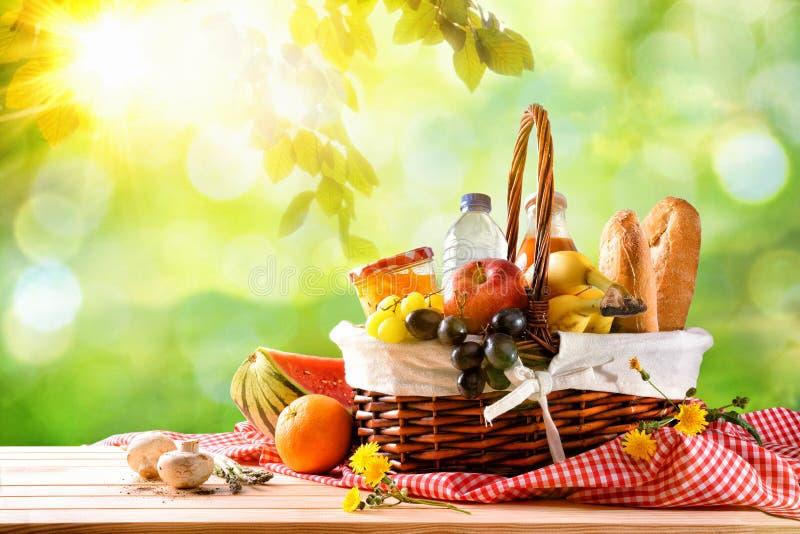 Cesta de vime do piquenique com alimento na tabela no campo imagens de stock royalty free