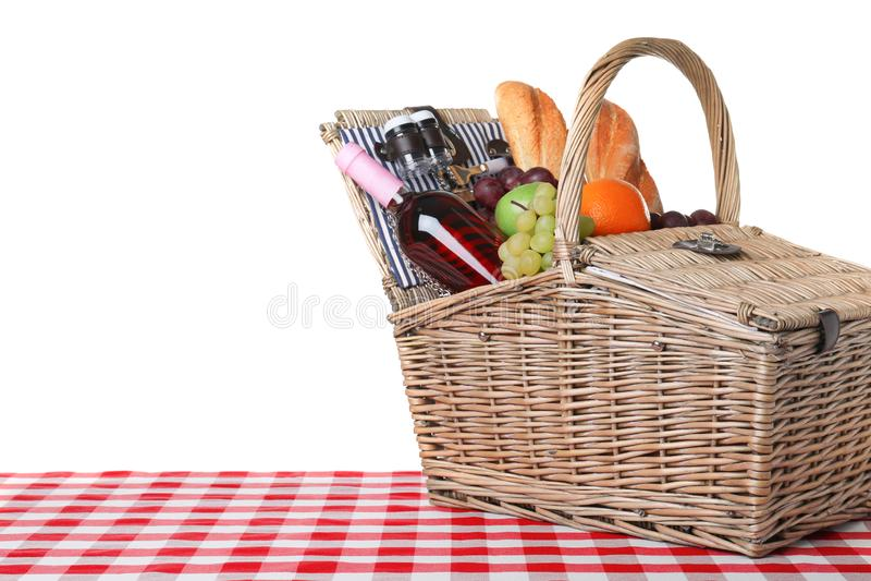 Cesta de vime do piquenique com os produtos diferentes na toalha de mesa quadriculado contra o fundo branco, espaço para foto de stock royalty free