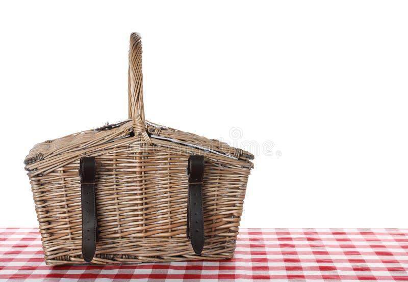 Cesta de vime fechado do piquenique na toalha de mesa quadriculado contra o branco fotos de stock royalty free