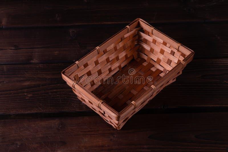 Cesta de vime vazia em um fundo de madeira imagens de stock royalty free