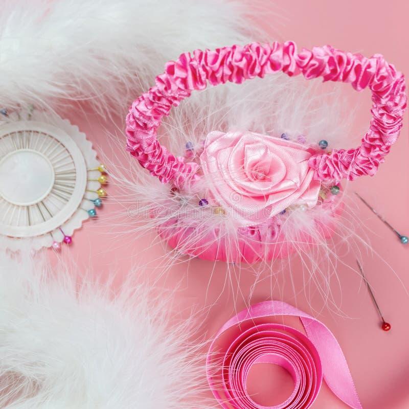 Cesta decorativa de fitas do cetim e da pele macia branca em um fundo cor-de-rosa Trabalho manual imagem de stock