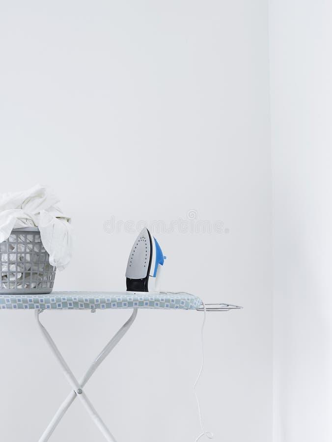 Cesta del hierro y de lavadero en el tablero que plancha contra la pared blanca imagen de archivo