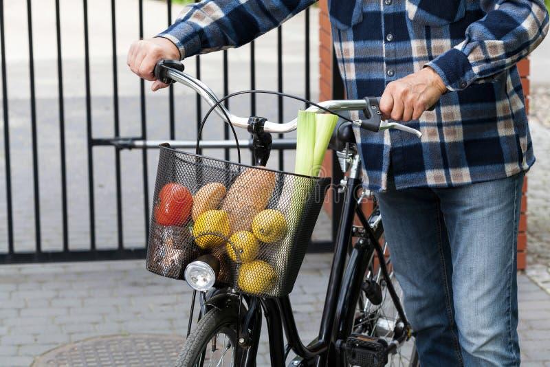 Cesta del hombre y de la bicicleta por completo de ultramarinos imágenes de archivo libres de regalías