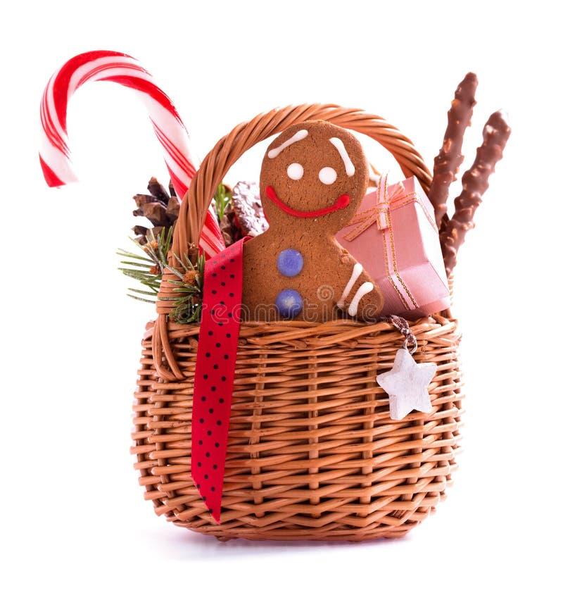 Cesta del regalo de la Navidad con las invitaciones y el hombre de pan de jengibre aislados foto de archivo