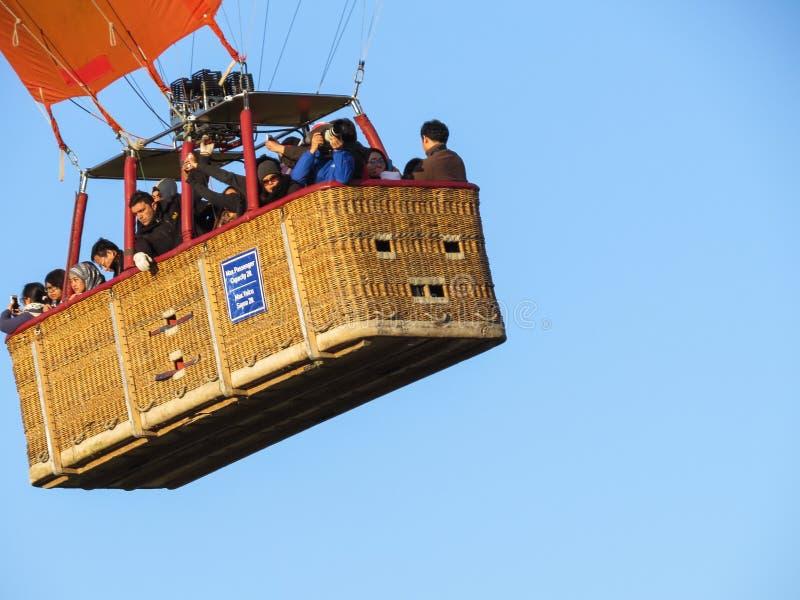 Cesta do balão com piloto e turistas no céu azul Lugar para o texto foto de stock