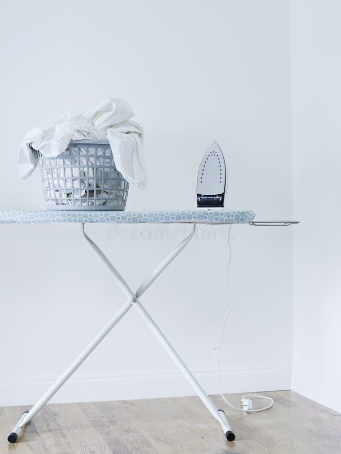 Cesta do ferro e de lavanderia na tábua de passar a ferro contra a parede branca imagens de stock royalty free