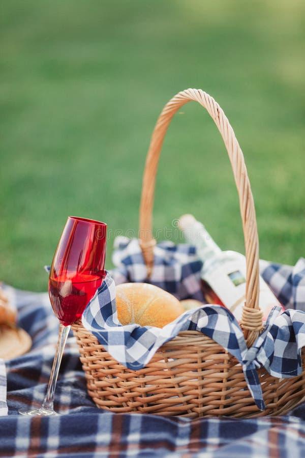 Cesta do piquenique com bebidas, alimento e fruto na parte externa da grama verde no parque do verão imagens de stock