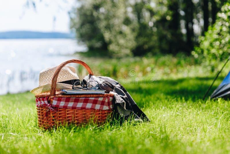Cesta do piquenique com chapéu, livro e gramas na grama no dia ensolarado do verão imagem de stock