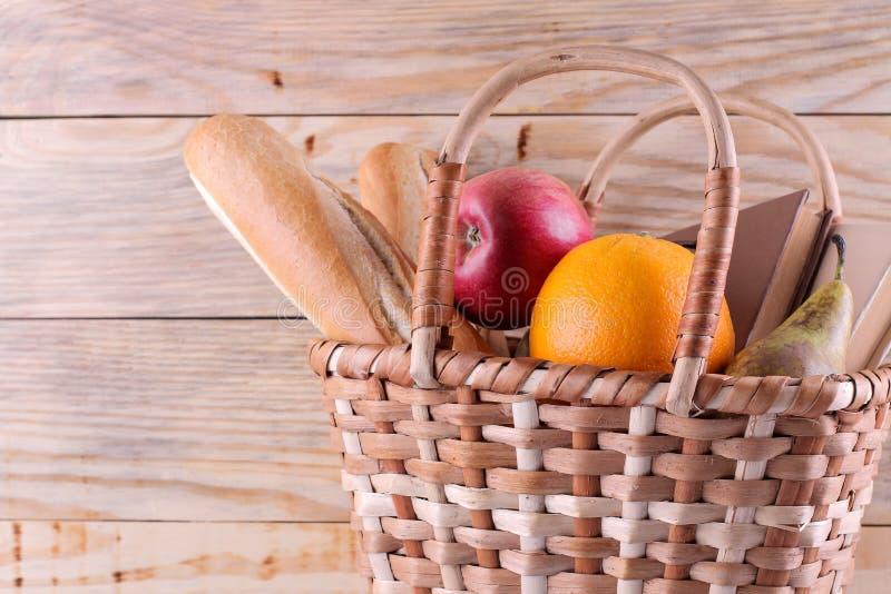 Cesta do piquenique com fruto do vinho e outros produtos em um fundo de madeira natural Resto do ver?o acampar Piquenique na natu fotos de stock royalty free