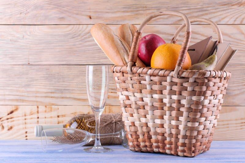 Cesta do piquenique com fruto do vinho e outros produtos em um fundo de madeira natural Resto do ver?o acampar Piquenique na natu imagens de stock royalty free