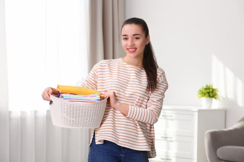 Cesta feliz de la tenencia de la mujer joven con el lavadero imagen de archivo