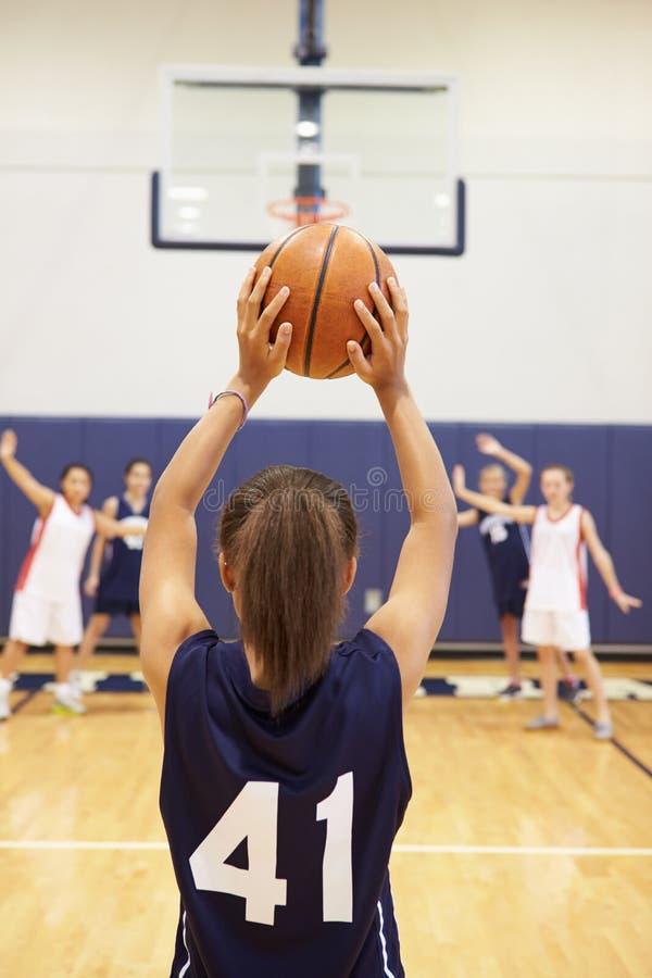 Cesta femenina del tiroteo del jugador de básquet de la High School secundaria fotos de archivo libres de regalías